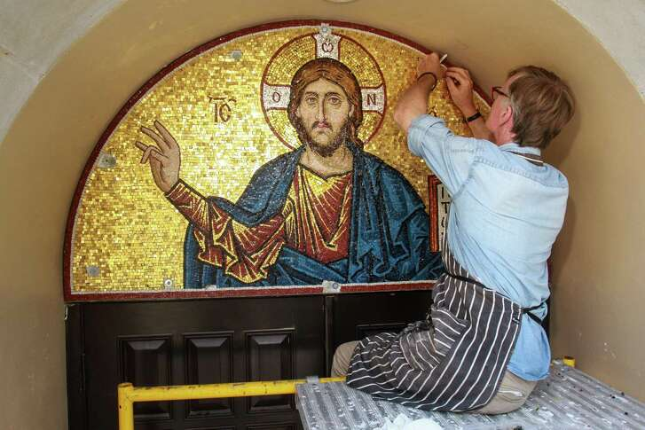 "British artist Aidan Hart works from a scaffold as he puts the finishing touches on his ""Christ Pantocrator"" mosaic on the outside of St. George Orthodox Church."