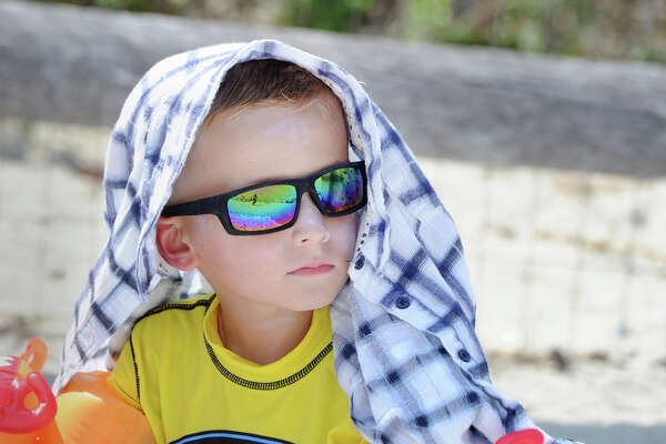 With the temperature in the mid-90s and hotter weather expected tomorrow, Andre Parchinsky, 6, of Greenwich, wore a shirt over his head and sunglasses as he attempted to stay cool at Greenwich Point, Conn., Tuesday, August 28, 2018.
