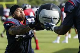 Guard Senio Kelemete gets a dose of medicine ball during a drill at Texans training camp.