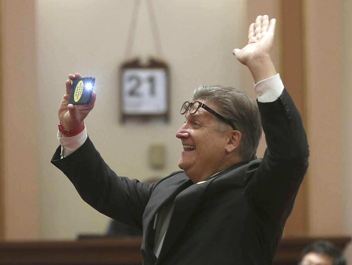 State Sen. Bob Hertzberg, D-Van Nuys, smiles and snaps a photo as the final votes are posted for passage of his bail reform bill by the state Senate, Tuesday, Aug. 21, 2018, in Sacramento, Calif. The bill now goes to Gov. Jerry Brown. (AP Photo/Rich Pedroncelli)