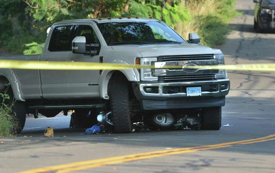 A motorcycle lays underneath a Ford pickup truck on Grandview Ave. after the rider was pulled out by emergency personnel and taken to Norwalk Hospital by ambulance on Tuesday August 28, 2018 in Norwalk Conn Photo: Alex Von Kleydorff / Hearst Connecticut Media / Norwalk Hour