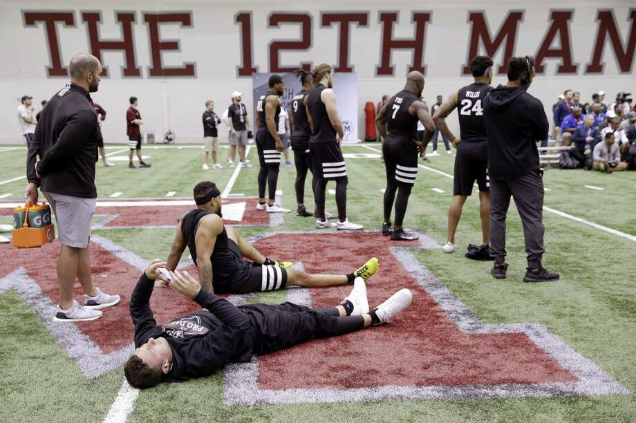 "In this March 27, 2018 file photo, former Cleveland Browns quarterback Johnny Manziel lies on the turf looking at his phone between drills, with Texas A&M's ""The 12th Man"" trademarked nickname for its sports fans on the wall, rear, at his alma mater during football Pro Day in College Station, Texas. The school, among several that aggressively protects it's trademark, forced a man in nearby Bellaire, Texas, to stop producing a beer he called 12th Can saying it was too similar to 12th Man. Photo: Michael Wyke /Associated Press / Copyright 2018 The Associated Press. All rights reserved"