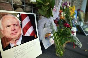 Photographs, flowers and notes gather at a makeshift memorial to Sen. John McCain outside his office in Phoenix, Arizona, on Sunday. McCain, who died Saturday at age 81. He will lie in state in the Capitol Rotunda in Phoenix and receive a full dress funeral service at the Washington National Cathedral.