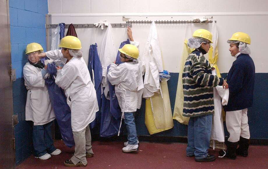 Hispanic Carolina Turkeys employees clown around, at left, while others prepare for their shifts at the Mt. Olive, NC, poultry processor. About 55 percent of the facility's workers are immigrants from Latin America. A recent Washington Post article about two white poultry workers feeling excluded caused a stir. Photo: BILLY CALZADA /SAN ANTONIO EXPRESS-NEWS / SAN ANTONIO EXPRESS-NEWS
