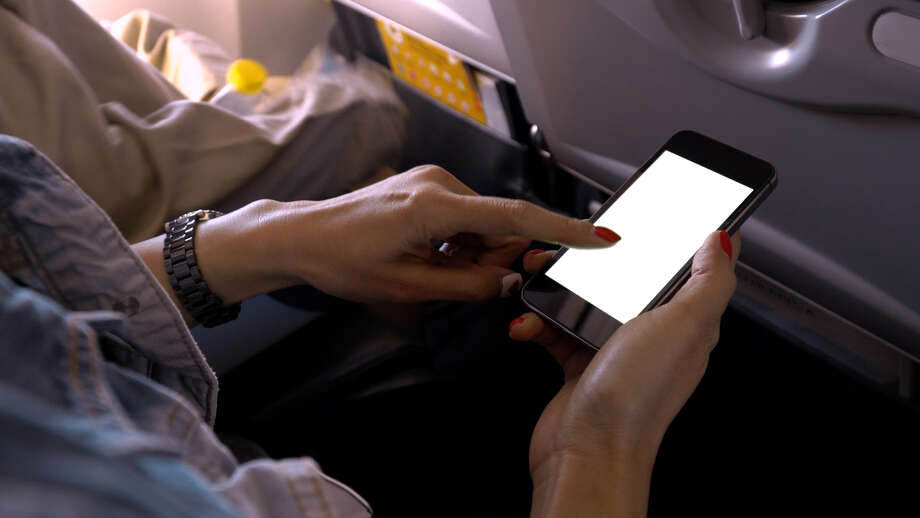 An airplane passenger uses a phone while on a flight. Photo: Pojcheewin Yaprasert / EyeEm