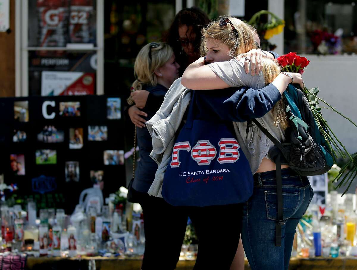 Mourners hug in front of the IV Deli Mart, where part of Friday night's mass shooting took place, on Tuesday, May 27, 2014 in the Isla Vista area near Goleta, Calif. Sheriff's officials said Elliot Rodger, 22, went on a rampage near the University of California, Santa Barbara, stabbing three people to death at his apartment before shooting and killing three more in a crime spree through a nearby neighborhood. (AP Photo/Chris Carlson)