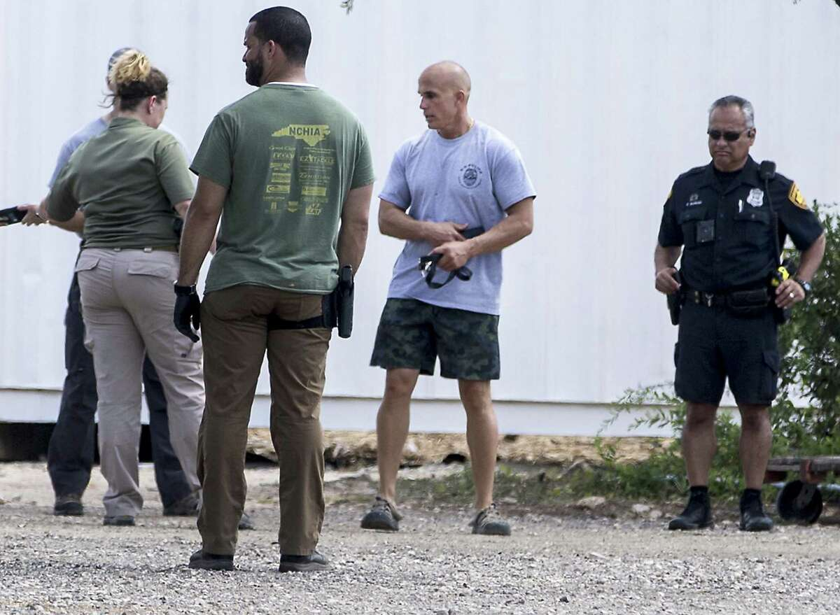 A man identified as Bradley Croft, second from right, talks with state and federal authorities serving a search warrant Wednesday, Aug. 8, 2018 at canine charity Universal K9, 15329 Tradesman, near Loop 1604 on the Northwest Side, as part of a federal investigation. Croft is a principal in Universal K9.
