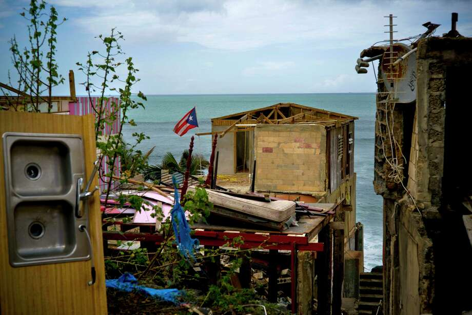 FILE - In this Oct. 5, 2017 file photo, a Puerto Rican national flag is mounted on debris of a damaged home in the aftermath of Hurricane Maria in the seaside slum La Perla, San Juan, Puerto Rico. An independent investigation ordered by Puerto Rico's government estimates that nearly 3,000 people died as a result of Hurricane Maria. The findings issued Tuesday, Aug. 28, 2018, by the Milken Institute School of Public Health at George Washington University contrast sharply with the official death toll of 64. (AP Photo/Ramon Espinosa) Photo: Ramon Espinosa / Copyright 2017 The Associated Press. All rights reserved.
