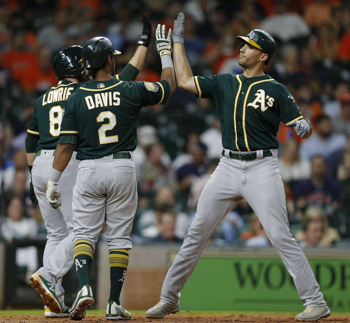 HOUSTON, TX - AUGUST 28: Matt Olson #28 of the Oakland Athletics receives high fives from Khris Davis #2 and Jed Lowrie #8 after hitting a home run in the third inning against the Houston Astros at Minute Maid Park on August 28, 2018 in Houston, Texas. (Photo by Bob Levey/Getty Images)