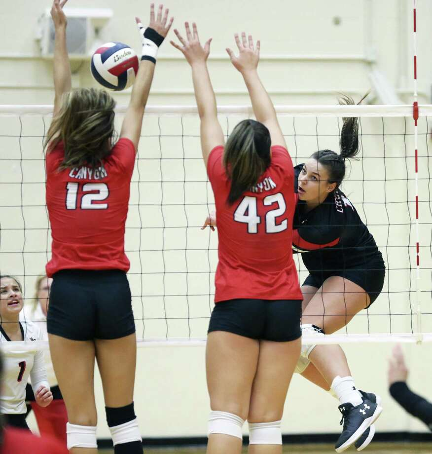 Churchill's Caroline Meuth fires the ball into Canyon blockers Angel Jones (12) and Erin Jones as Churchill hosts Canyon in volleyball at Littleton Gym on August 28, 2018. Photo: Tom Reel, Staff / Staff Photographer / 2017 SAN ANTONIO EXPRESS-NEWS