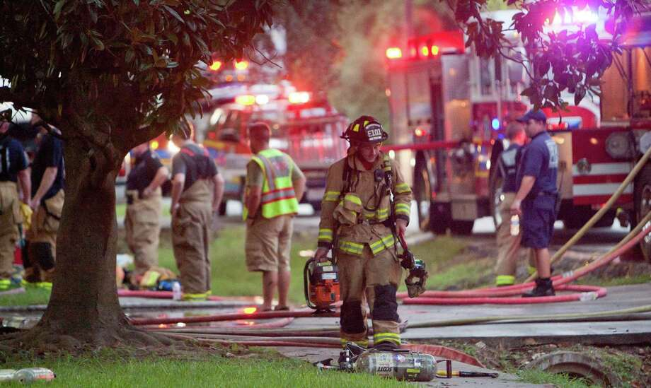 A firefighter walks through the scene of  a residential fire Tuesday at the 2500 block of Glen Loch Dr. in The Woodlands. Photo: Eric S. Swist / Staff Photo By Eric S. Swist / Staff photo by Eric S. Swist