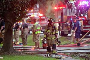 A firefighter walks through the scene of  a residential fire Tuesday at the 2500 block of Glen Loch Dr. in The Woodlands.