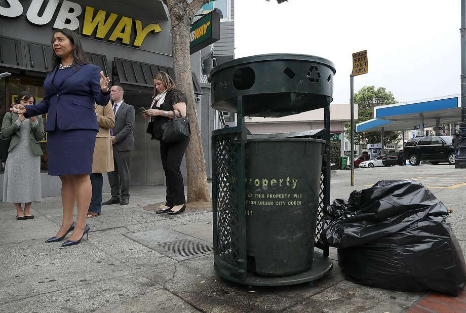 Mayor London Breed walks past one of the city's green trash cans in the Castro. Photo: Liz Hafalia / The Chronicle