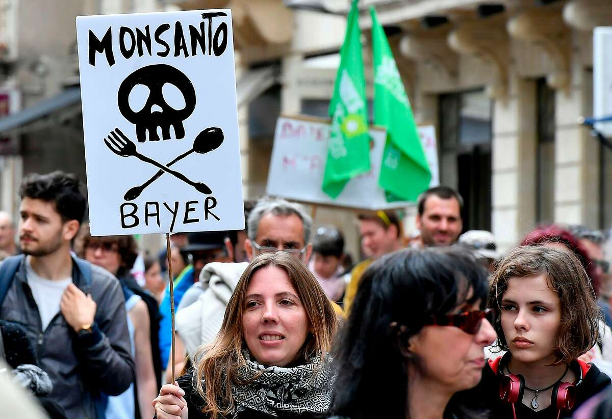 (FILES) In this file photo taken on May 20, 2017, demonstrators walk with placards during a march for agroecology and civil resistance against seed and pesticide maker Monsanto in Bordeaux, southwestern France. - A cancer victim's surprise court victory over US pesticide maker Monsanto could open the floodgates to a slew of similar lawsuits, potentially leaving the firm's new German owner Bayer with a major case of buyer's remorse. (Photo by GEORGES GOBET / AFP)GEORGES GOBET/AFP/Getty Images