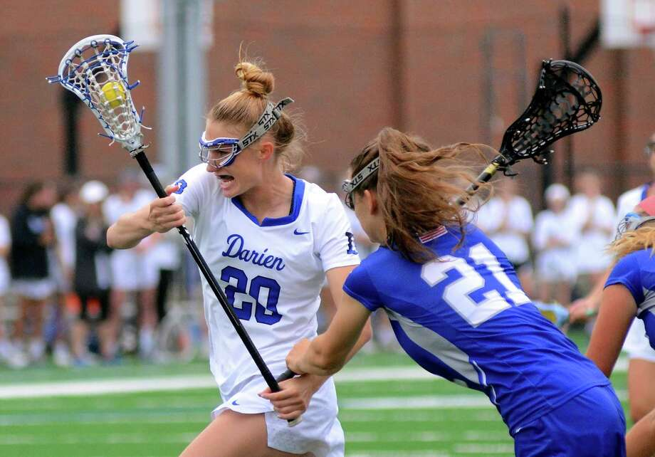 Darien's Katie Ramsay (20) looks to line up a goal shot as Fairfield Ludlowe's Amanda Schramm (21) tries to intercept during Class L girls lacrosse action. Photo: Christian Abraham / Hearst Connecticut Media