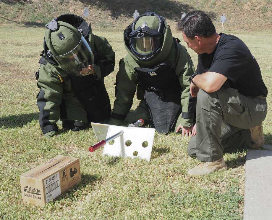 Midland Fire Marshall James Howard, who is  receiving EOD training to join the bomb squad, assist members of the media, including MRT online editor Mercedes Cordero, wearing the bomb suits, with placement of the PAN, a non-electric disruptor that fires a water blast, at the suspicious package after viewing a digital x-ray to determine where to aim the blast 08/29/18 during a media day with Midland Bomb Squad. Tim Fischer/Reporter-Telegram Photo: Tim Fischer/Midland Reporter-Telegram
