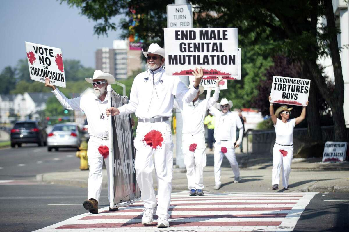 Harry Guiremand, of Kapaa, Hawaii, leads a group of Bloodstained Men members across Washington Boulevard while protesting male circumcision in downtown Stamford Aug. 7.