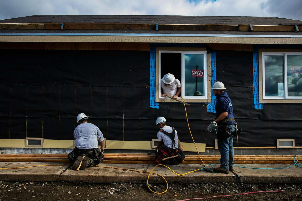 (l-r) Construction workers Victor Villanueva, Jared Ashworth, Rob Williams and Jesse Merritt work together to rebuild displaced resident Dan Bradford's (not pictured) home in the Coffey Park neighborhood of Santa Rosa, California, on Monday, Jan. 22, 2018. Dan Bradford's home is the first one in the neighborhood to be rebuilt after the Tubbs fire tore ravaged thousands of homes last October.