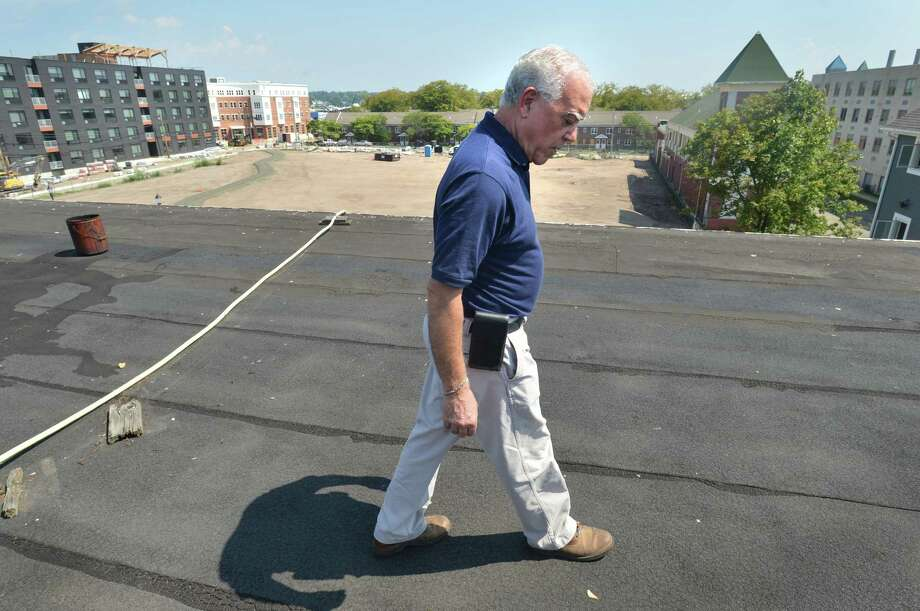 Mike Sgobbo, Property Manager with the Norwalk Building Management Department walks gently over areas of the roof of the South Norwalk Community Center that are failing on Wednesday August 29, 2018 in Norwalk Conn.  The Common Council has authorized the city to purchase the remaining half interest in the building at 98 South Main St. from South Norwalk Community Center, Inc. Photo: Alex Von Kleydorff, Hearst Connecticut Media / Norwalk Hour