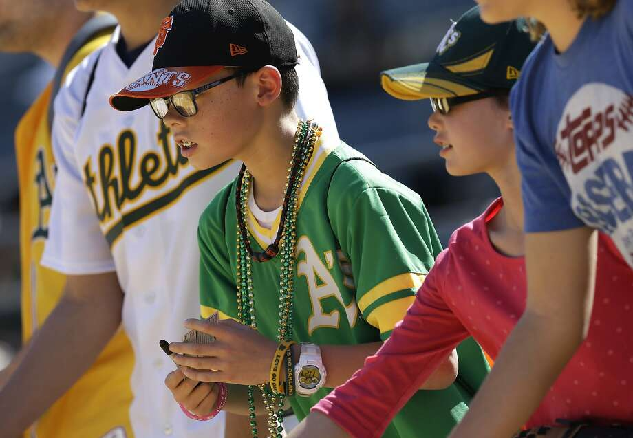 Oakland Athletics fans view batting practice prior to a spring training exhibition baseball game against the San Francisco Giants Saturday, March 14, 2015, in Mesa, Ariz. (AP Photo/Ben Margot) Photo: Ben Margot / AP