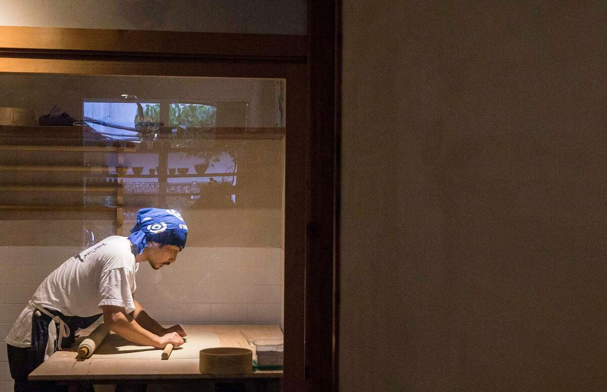 Koichi Ishii rolls out dough for traditional hand made soba noodles inside a sealed glass room in the early morning hours at Soba Ichi in Oakland, Calif. Wednesday, Aug. 15, 2018.