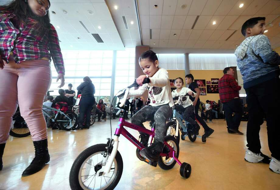 In this file photo, Taysha Claudio watches her daughters, Mikaella Jimenez, 4, and Alanna Jimenez, 5, try out their new bicycles during a Three Kings Day event at the John C. Daniels Interdistrict Magnet School of International Communication in New Haven in January. Claudio and her daughters moved to New Haven from Puerto Rico in October after Hurricane Maria. Photo: Arnold Gold / Hearst Connecticut Media / New Haven Register