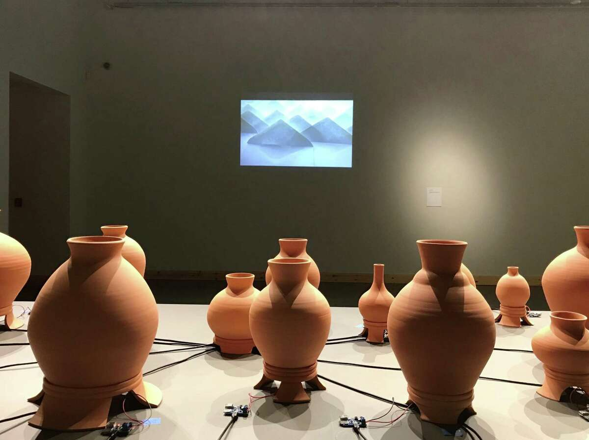 """Raheleh Filsoofi's video """"... still traveling... """" on a wall behind a detail of """"The Inh(a/i)bited Space,"""" part of her installation at the University of Houston Downtown's O'Kane Gallery."""