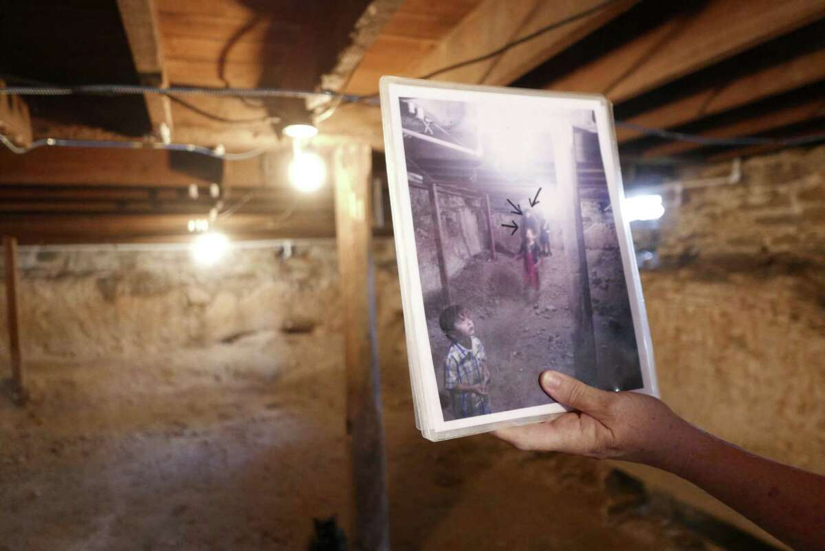 Erin O. Wallace-Ghedi displays a picture marked with arrows showing the alleged appearance of a ghost in the basement of the Magnolia Hotel in Seguin. The basement was once used as a shelter from Indian raids and as a jail.