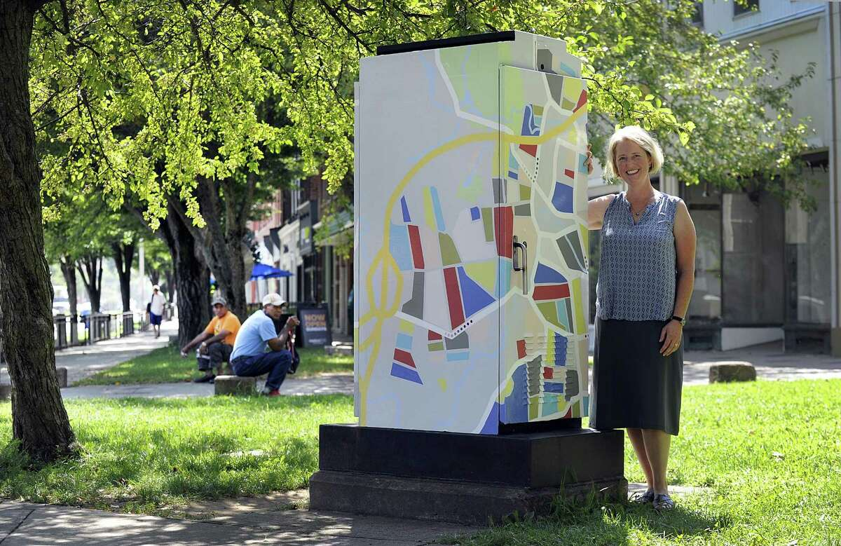 Toni Miraldi of Newtown stands with the artwork that she designed for a traffic box at the corner of Main and Elm Streets in Danbury, Wednesday, August 29, 2018.