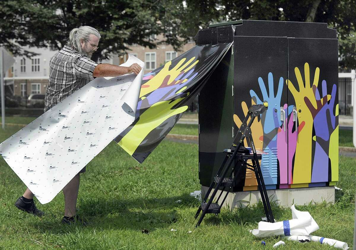 Owen Trellis of Merritt Big Color, covers a traffic box with a design by Tracy Biagiarelli of Redding, Monday, August 27, 2018. The box is at the corner of Kennedy and Elm Street in Danbury.