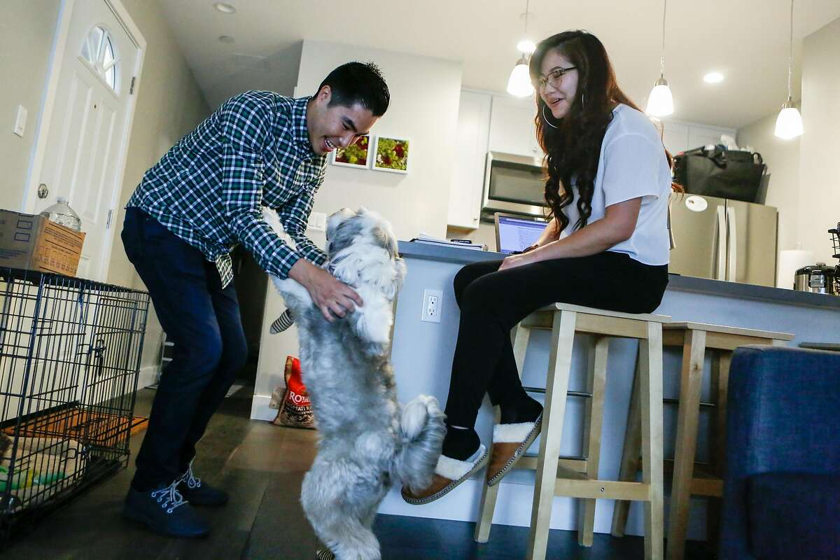 Derek Flores plays with tenant Alex Mercando's dog, Misty, as they discuss the ADU which Mercando and her family occupy in the Richmond area on Wednesday, August 29, 2018 in San Francisco, Calif.