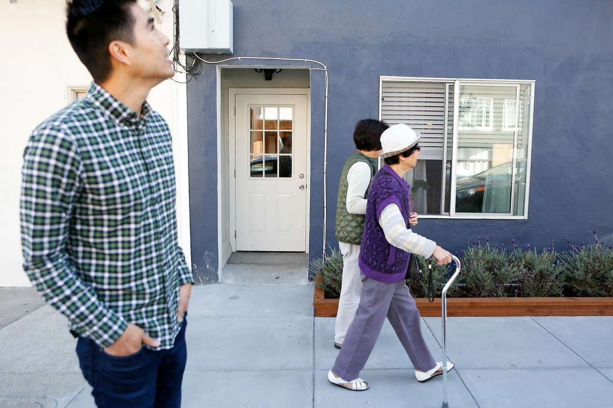 Owner Derek Flores looks up as his building as two neighbors walk by on Wednesday, August 29, 2018 in the Richmond are of San Francisco, Calif.