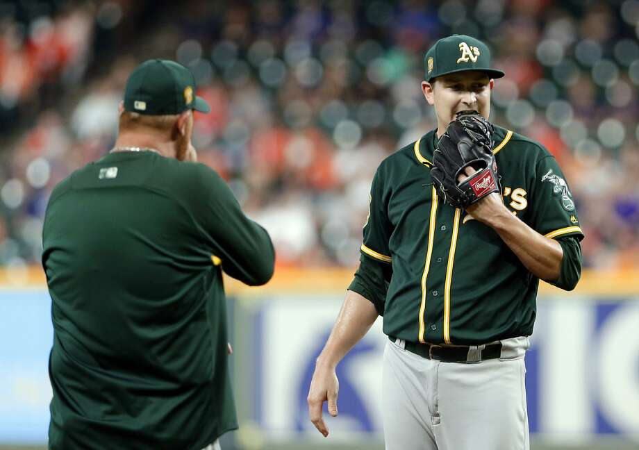 Oakland Athletics starting pitcher Trevor Cahill, right, bites his glove as pitching coach Scott Emerson, left, heads to the mound for a conference after the Houston Astros score two runs during the first inning of a baseball game Wednesday, Aug. 29, 2018, in Houston. Photo: Michael Wyke / Associated Press