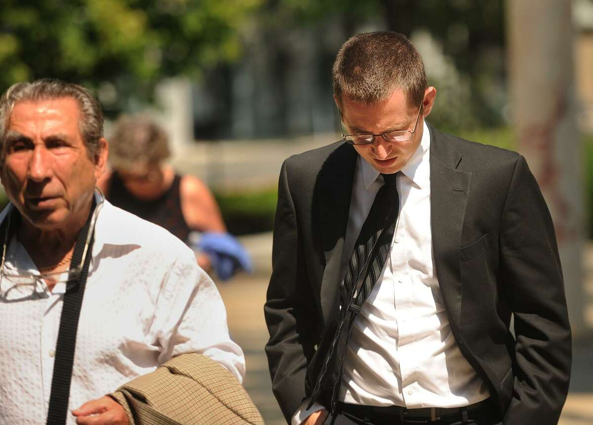 George Garofano, right, of North Branford, keeps his eyes down as he walks into Federal Court in Bridgeport, Conn. for sentencing in the high profile nude photo hacking case dubbed
