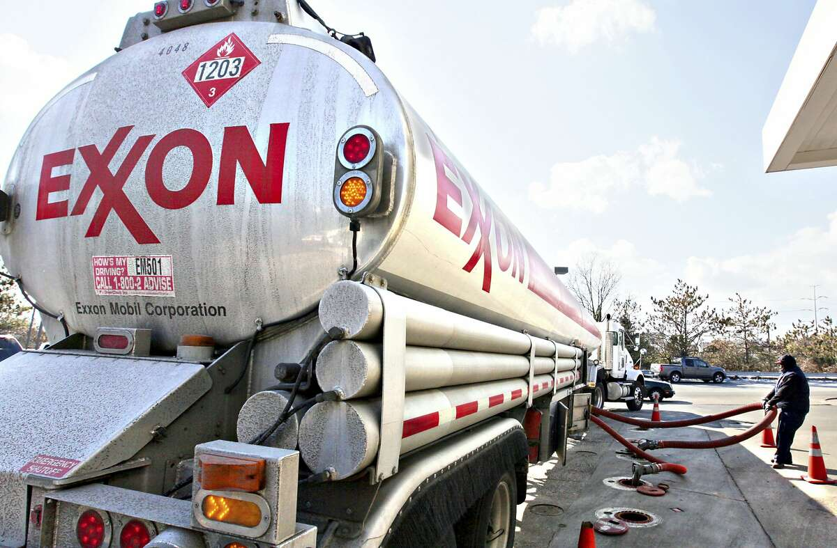 FILE - In this Jan. 30, 2009, file photo, an Exxon tanker truck operated by Corey Moorer, right, of Clinton, Md., makes a refueling stop at an Exxon station in Arlington, Va.