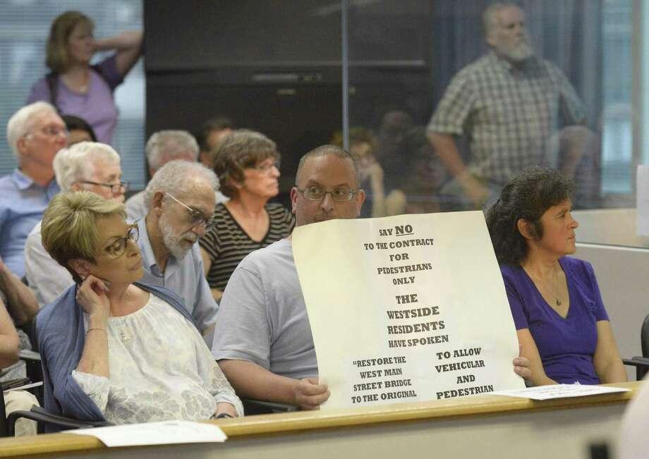 Michael Pellicci holds a sign as he and Fran Caminiti, at left, attend a public hearing about the planned rehabilitation of the 130-year-old West Main Street bridge on August 28, 2018 in Stamford, Connecticut. Pellicci, a business owner on the Stamford's West Side, along with residents want the bridge to be restored to accommodate cars to link their neighborhood to downtown and help it thrive. Park advocates want the bridge to remain a walk-only, to preserve the feel of the greenway now being restored. Photo: Matthew Brown / Hearst Connecticut Media / Stamford Advocate