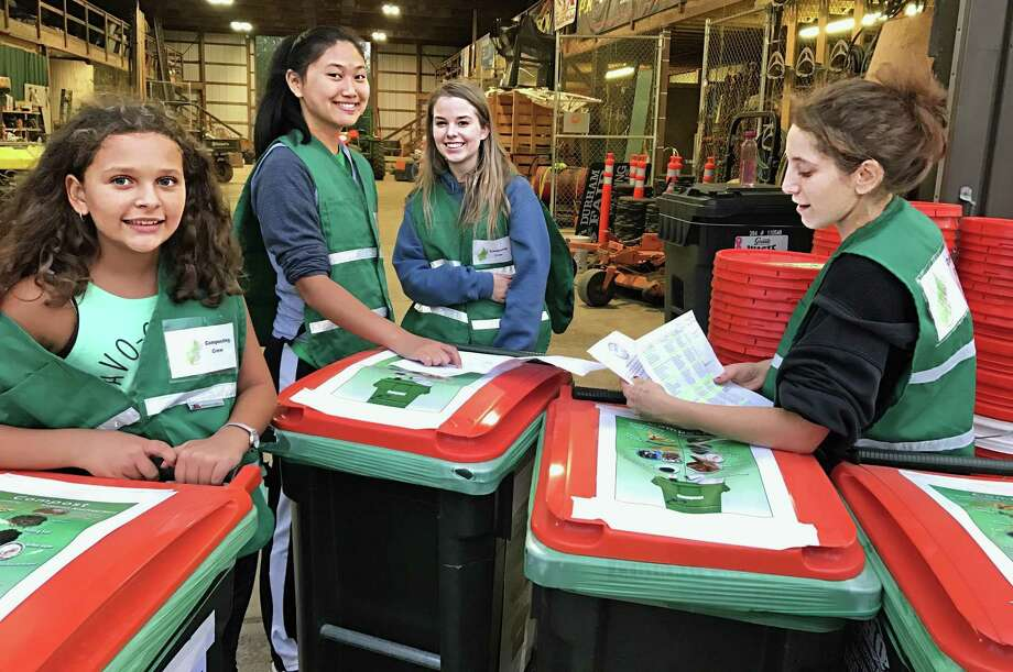 There is a new green initiative at the Durham Fair this year, which includes newly installed solar panels, water-filling stations and a compost crew that gathers organic waste from those selling food at the event. Here, members of Coginchaug Regional High School's Environmental Coginchaug Organization and community volunteers set up compost bins which will be distributed to vendors. Photo: Contributed Photo