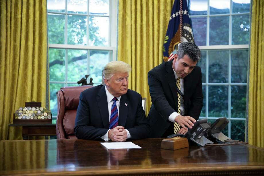 A White House aide assists President Donald Trump connect a phone call with Enrique Pena Nieto, Mexico's president, not pictured, in the Oval Office of the White House on Monday. Trump said he would terminate the North American Free Trade Agreement and sign a new trade accord with Mexico, potentially leaving Canada out of the bloc. Photo: Al Drago /Bloomberg / © 2018 Bloomberg Finance LP