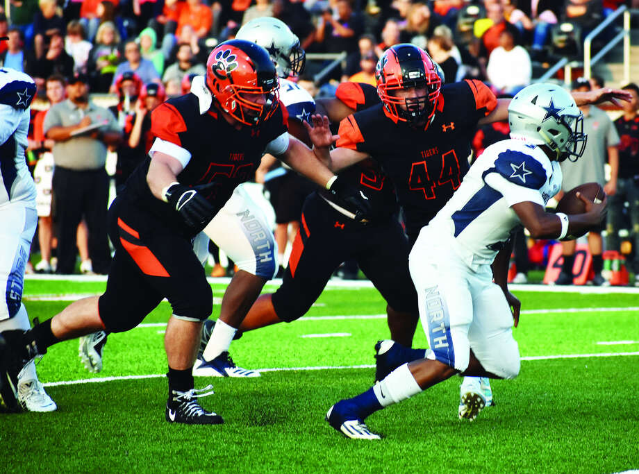 Edwardsville's Connor Hinterser, left, and Ryan Strohmeier, middle, track down the McCluer North ball carrier during the first quarter of Friday's season opener. Photo: Matthew Kamp