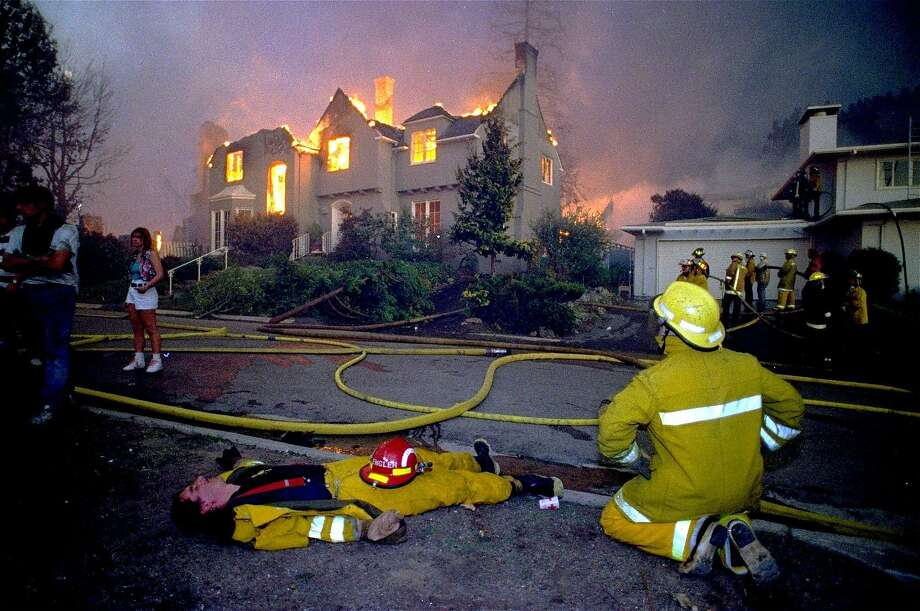 A firefighter keeps an eye on his partner sprawled on a lawn and recovering from exhaustion while other firefighters continue to battle blazes in a residential area in the Oakland hills in 1991. Photo: Glen Morimoto / Associated Press 1991