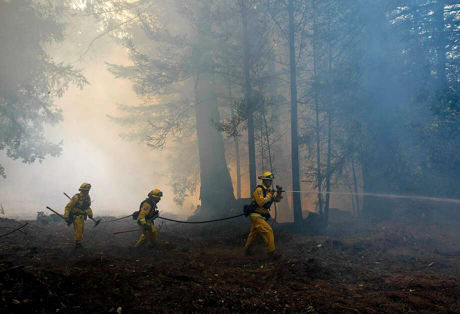 Matt Ramsey (left), David Lutz and Chris Leddy search for hot spots along Warnella Road as firefighters battle the Lockheed Fire that was caused by a campfire burning out of control in Santa Cruz County in 2009. Photo: Michael Macor / The Chronicle 2009