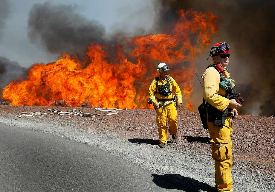 Firefighters back away from the flames as they approach Summit Road, battling the Morgan Fire burning over the summit of Mount Diablo State Park in 2013. Photo: Brant Ward / The Chronicle 2013