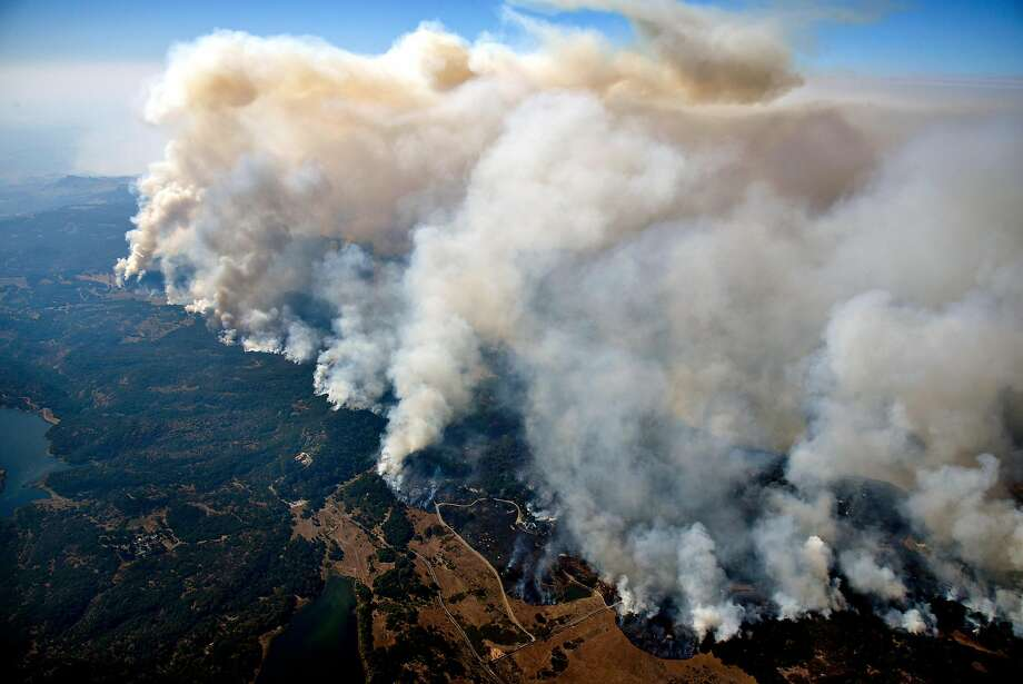 Columns of smoke rise from the Atlas Fire as it burns in the hills east of Napa in 2017. The blaze started when a tree and tree limb fell on a PG&E power line at separate spots. Photo: Michael Short / Special To The Chronicle 2017