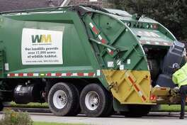 Waste Management workers pickup trash in a Spring, Texas neighborhood.