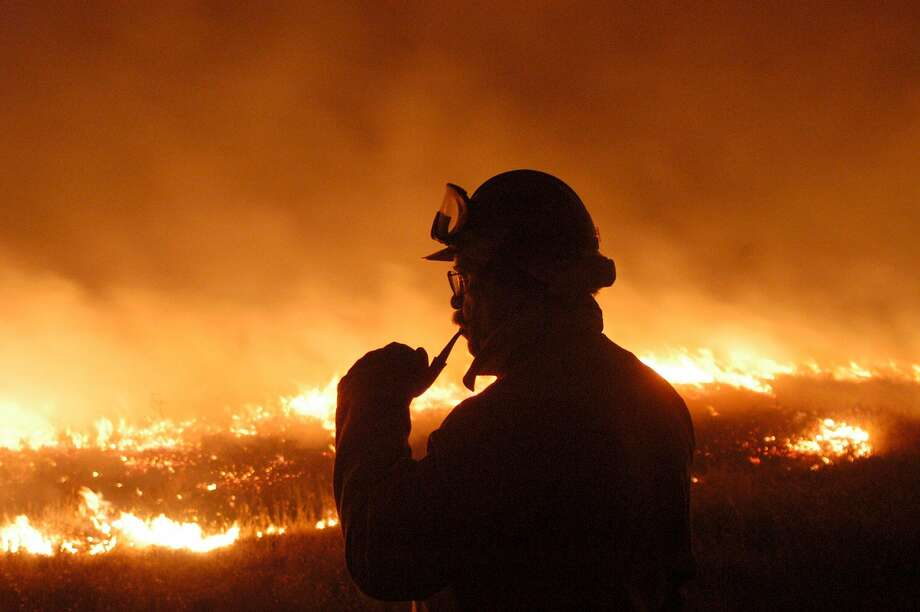 Julian CDF fire chief Skip Cabel smokes his pipe as he watches the Cedar Fire move past a home on the outskirts of Julian, Calif., Wednesday, Oct. 29, 2003.  (AP Photo/Imperial Valley Press, Paul H. Nilson)  HOUCHRON CAPTION  (10/31/2003):  Skip Cabel, a fire chief with the California Department of Forestry, watches the Cedar fire near Julian, Calif. Photo: PAUL H NILSON / AP