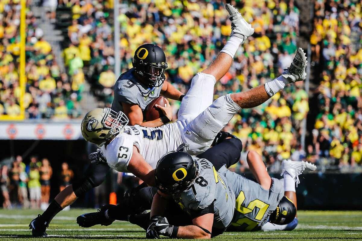 Oregon quarterback Dakota Prukop (9), avoids a collision as UC Davis linebacker Russell Reeder (53) and Oregon offensive lineman Cameron Hunt (78) tangle during an NCAA college football game in Eugene, Ore., Saturday, Sept. 3, 2016. Oregon won 53-28. (AP Photo/Thomas Boyd)