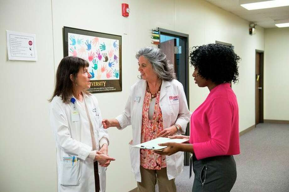 From left, Dorothy Lee, a retired SVSU associate professor of nursing and a current nurse practitioner at The Bay Community Health Clinic; Kathleen Schachman, SVSU's Harvey Randall Wickes Endowed Chair in Nursing and a nurse practitioner at the clinic; and LaToya Colvin, a social worker at the clinic, exchange notes at the clinic in 2017. (Photo provided/SVSU, Michael Randolph)