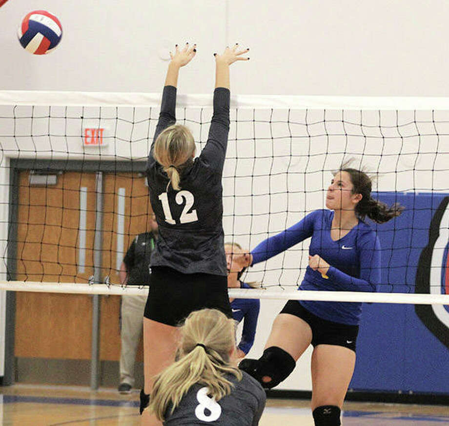 Roxana's Kiley Winfree (right) hits past the block of Calhoun's Alexis Klocke (12) during play at the Roxana Tournament earlier this month. The Shells were in Breese on Wednesday and lost to seven-state champion Mater Dei in two sets. Photo: Greg Shashack / The Telegraph