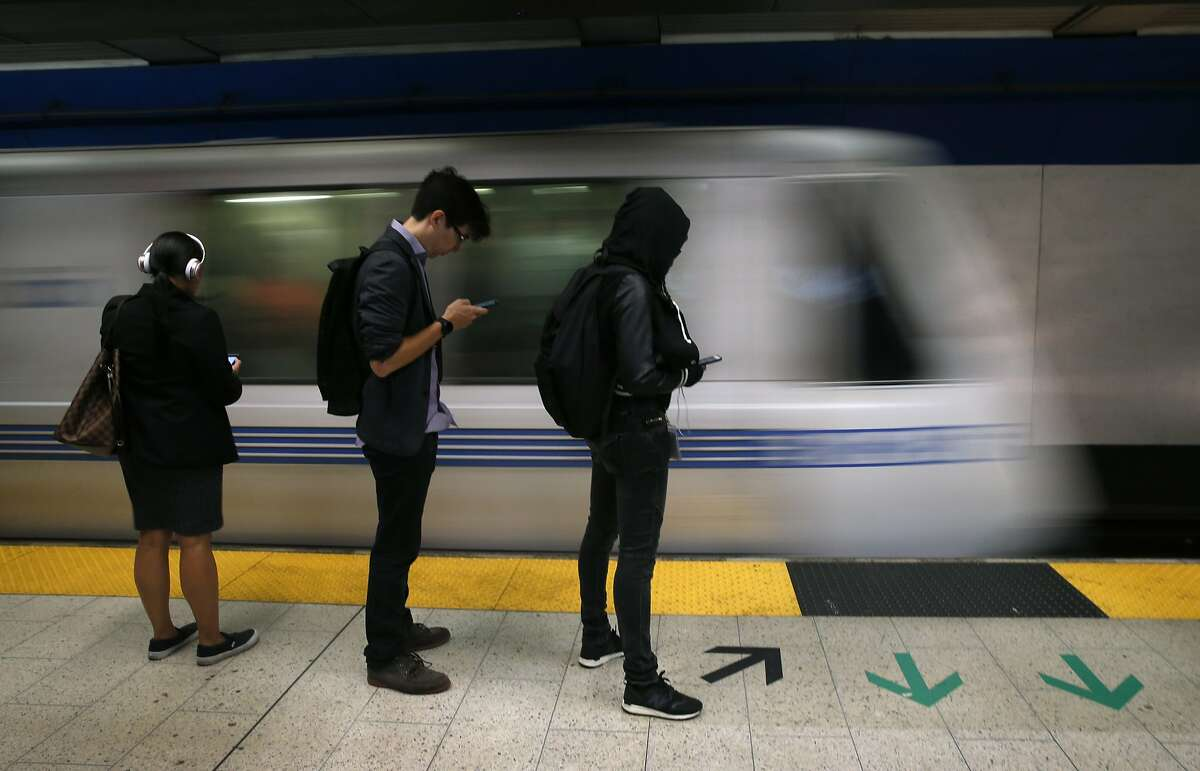 FILE-- Commuters wait on the plaform as a train arrives at the 19th Street BART station in Oakland, Calif. on Thursday, Aug. 2, 2018. BART riders can expect laborious bay crossings this holiday weekend as the transit system again shuts down service between West Oakland station and the 19th Street and Lake Merritt stations.