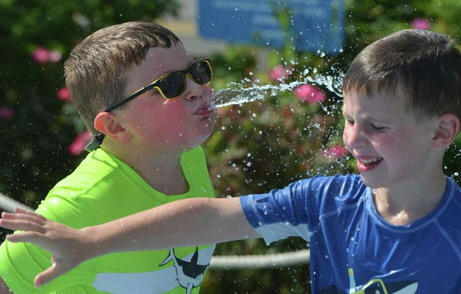 Declan McMullen sprays his friend Jaxton Healy while cooling at the splash pad at Calf Pasture Beach on Tuesday in Norwalk. Photo: Alex Von Kleydorff / Hearst Connecticut Media / Norwalk Hour